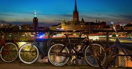 Bicycles parked at Slussen at night in Stockholm, with the city hall in background